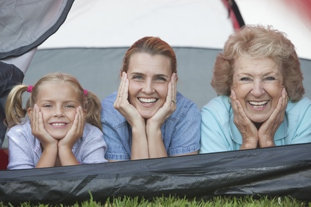 Mother daughter and grand-daughter lean on elbows smiling from tent