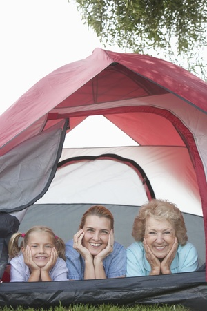 Mother daughter and grand-daughter lean on elbows smiling from tent Stock Photo - 12737617