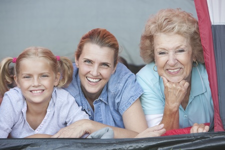 Mother daughter and grand-daughter smiling from tent Stock Photo - 12737618