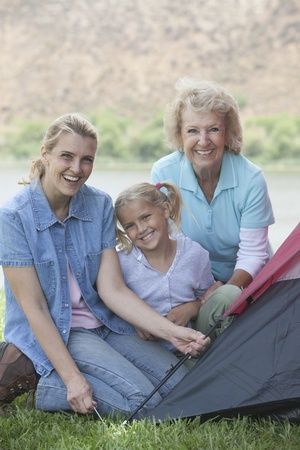 Mother daughter and grand-daughter putting up a tent Stock Photo - 12737620