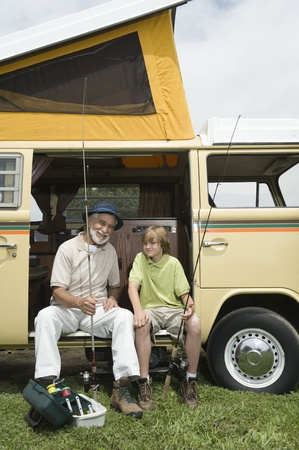 grand son: Grandfather and grandson sit with fishing rods in campervan
