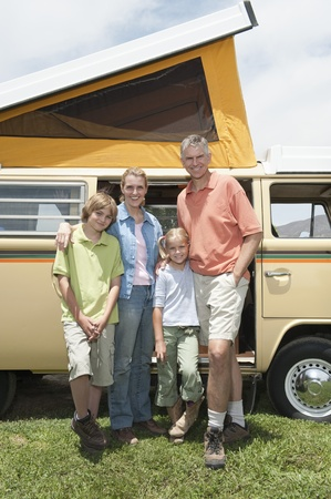 Family of four stand at campervan Stock Photo - 12735580