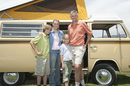 campervan: Family of four stand at campervan