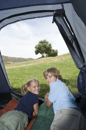camping pitch: Brother and sister lie in a tent looking back over their shoulders