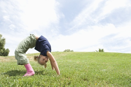 BACKFLIP: Bending over backwards girl on grass LANG_EVOIMAGES