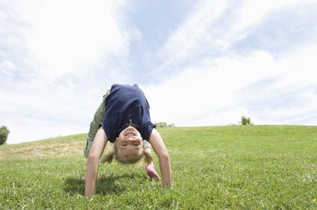 Bending over backwards girl on grass Stock Photo - 12737625