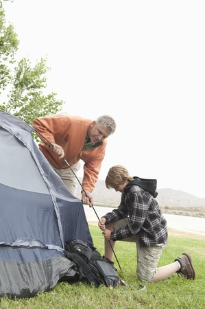 camping pitch: Father and son pitch a tent