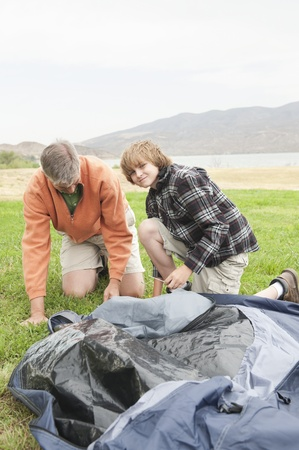 Father and son pitch a tent Stock Photo - 12735589
