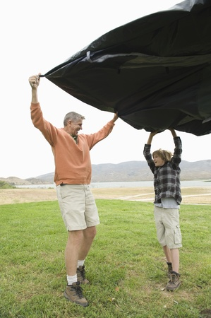 Father and son hold groundsheet in wind Stock Photo - 12735591