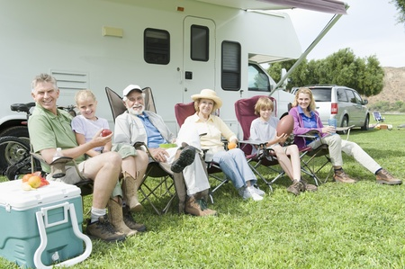recreational vehicle: Family sitting outside RV home