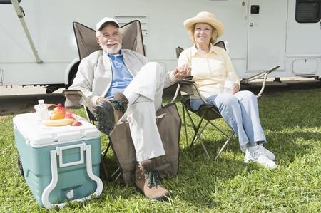 folding chair: Senior couple sit outside RV home