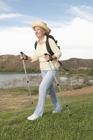 Senior woman orienteering with walking poles Stock Photo - 12737633