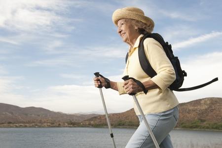 Senior woman orienteering with walking poles Stock Photo - 12737634