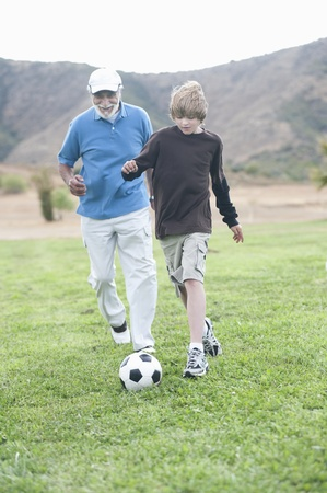 Grandfather and grand-son playing football Stock Photo - 12737636