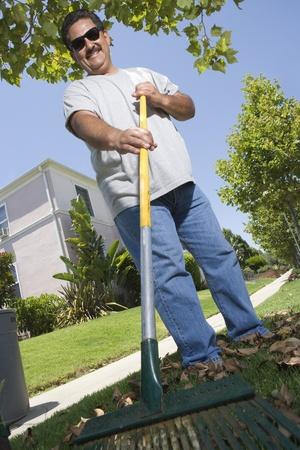 middle easterners: Portrait of man raking lawn in garden