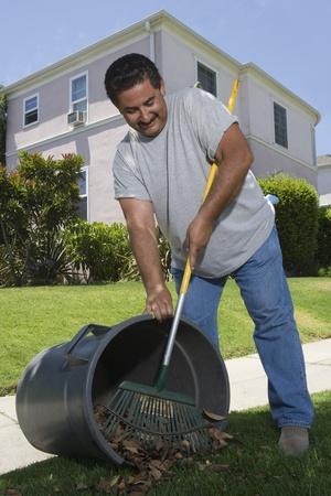 middle easterners: Man raking leaves in garden