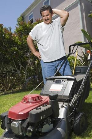 middle easterners: Man observing lawn mower in garden LANG_EVOIMAGES