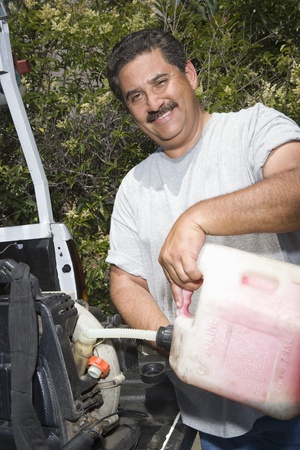 middle easterners: Portrait of man pouring fuel into lawn mower LANG_EVOIMAGES