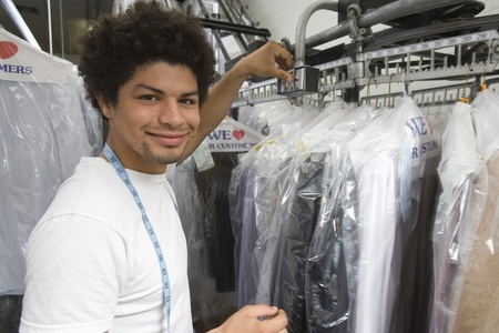 clothes rail: Portrait of young man working in dry cleaners LANG_EVOIMAGES
