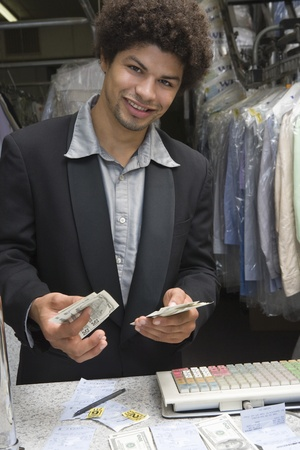 dry cleaners: Portrait of young man working in dry cleaners LANG_EVOIMAGES
