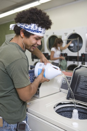 launderette: Young man washing clothes at launderette