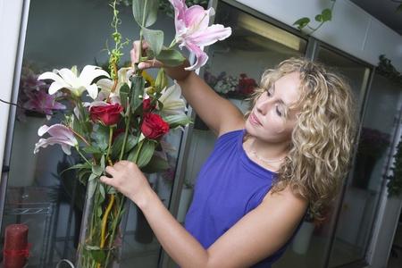 Female florist arranging flowers in vase Imagens