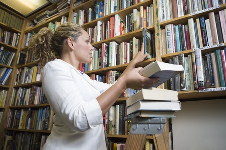 Female librarian putting books on shelves