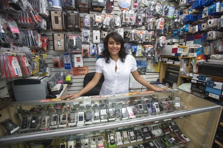 Portrait of young woman working in mobile phone shop Stock Photo - 12735646