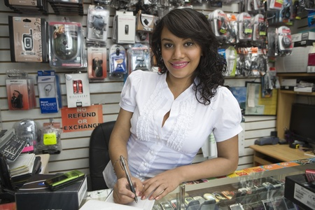 Portrait of young woman working in mobile phone shop Stock Photo - 12735648