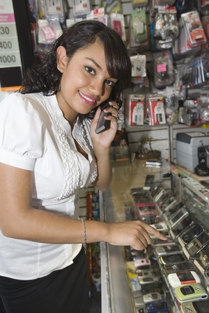 Portrait of young woman using mobile phone in shop Stock Photo - 12735632
