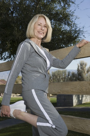 Mature woman stretches leg in warm up exercise Stock Photo - 12737690