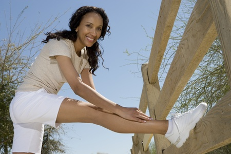 Mid adult woman stretches hamstring against fence Stock Photo - 12735272