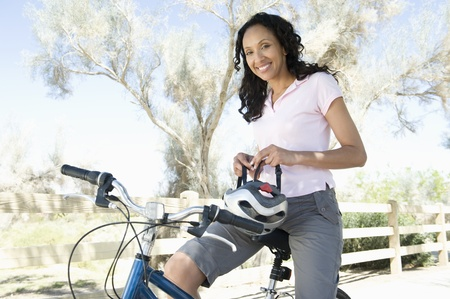 Woman adjusts cycling helmet on mountain bike Stock Photo - 12735627