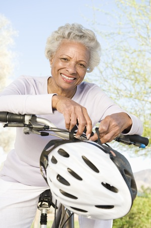 Senior woman leans on handlebars of mountain bike Stock Photo - 12735616