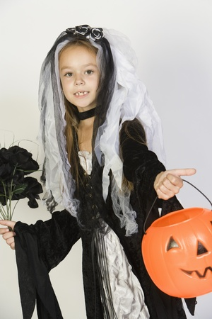 Portrait of girl (7-9) wearing Halloween costume with jack-o-lantern Stock Photo - 12735676