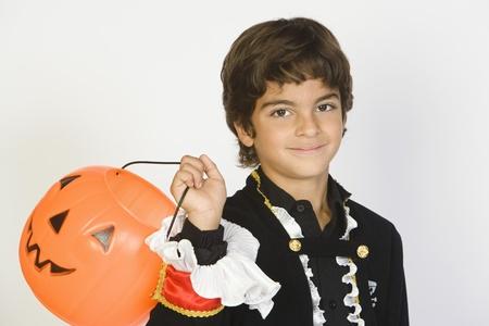 jackolantern: Portrait of boy (7-9) wearing Halloween costume with jack-o-lantern LANG_EVOIMAGES