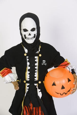 Portrait of boy (7-9) wearing skeleton mask with jack-o-lantern Stock Photo - 12735663