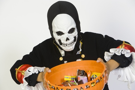 Portrait of boy (7-9) wearing skeleton mask holding candy bowl Stock Photo - 12735626