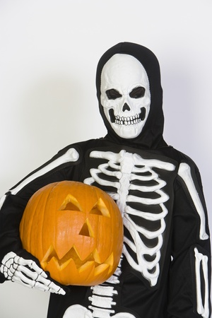 Portrait of child (7-9) wearing skeleton costume with jack-o-lantern Stock Photo - 12737698