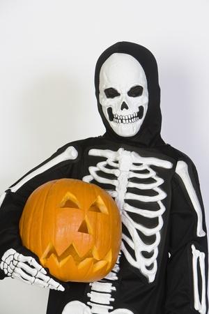 jackolantern: Portrait of child (7-9) wearing skeleton costume with jack-o-lantern LANG_EVOIMAGES