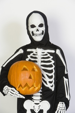 jackolantern: Portrait of child (7-9) wearing skeleton costume with jack-o-lantern LANG_EVOIMAGES