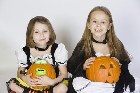 Portrait of girls (7-9) wearing Halloween costumes with jack-o-lanterns Stock Photo - 12737702