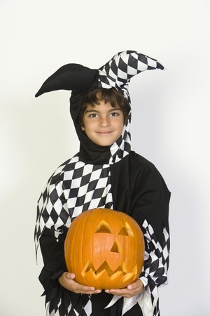 jackolantern: Portrait of boy (7-9) wearing jester costume with jack-o-lantern