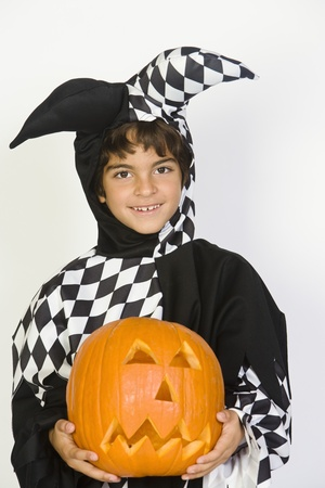 Portrait of boy (7-9) wearing jester costume with jack-o-lantern Stock Photo - 12737704
