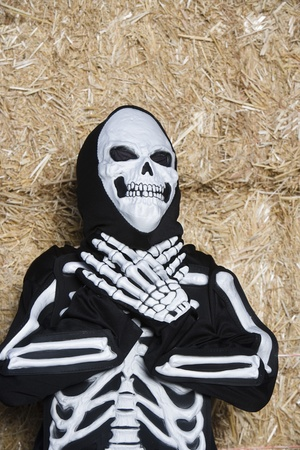 Portrait of child (7-9) wearing skeleton costume by hay Stock Photo - 12737707