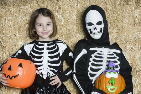 dressing up costume: Portrait of girls (7-9) wearing skeleton costumes with jack-o-lanterns