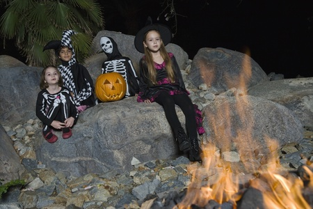 Portrait of boys and girls (7-9) wearing Halloween costumes by campfire Stock Photo - 12737711