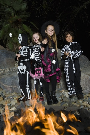 skeleton costume: Girls and boys (7-9) wearing Halloween costumes cooking marshmallows on campfire LANG_EVOIMAGES