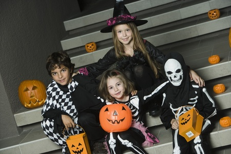 dressing up costume: Portrait of boys and girls (7-9) wearing Halloween costumes on steps