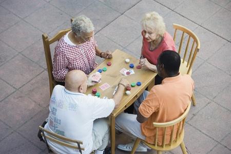 Senior people playing cards smiling Stock Photo - 12737723